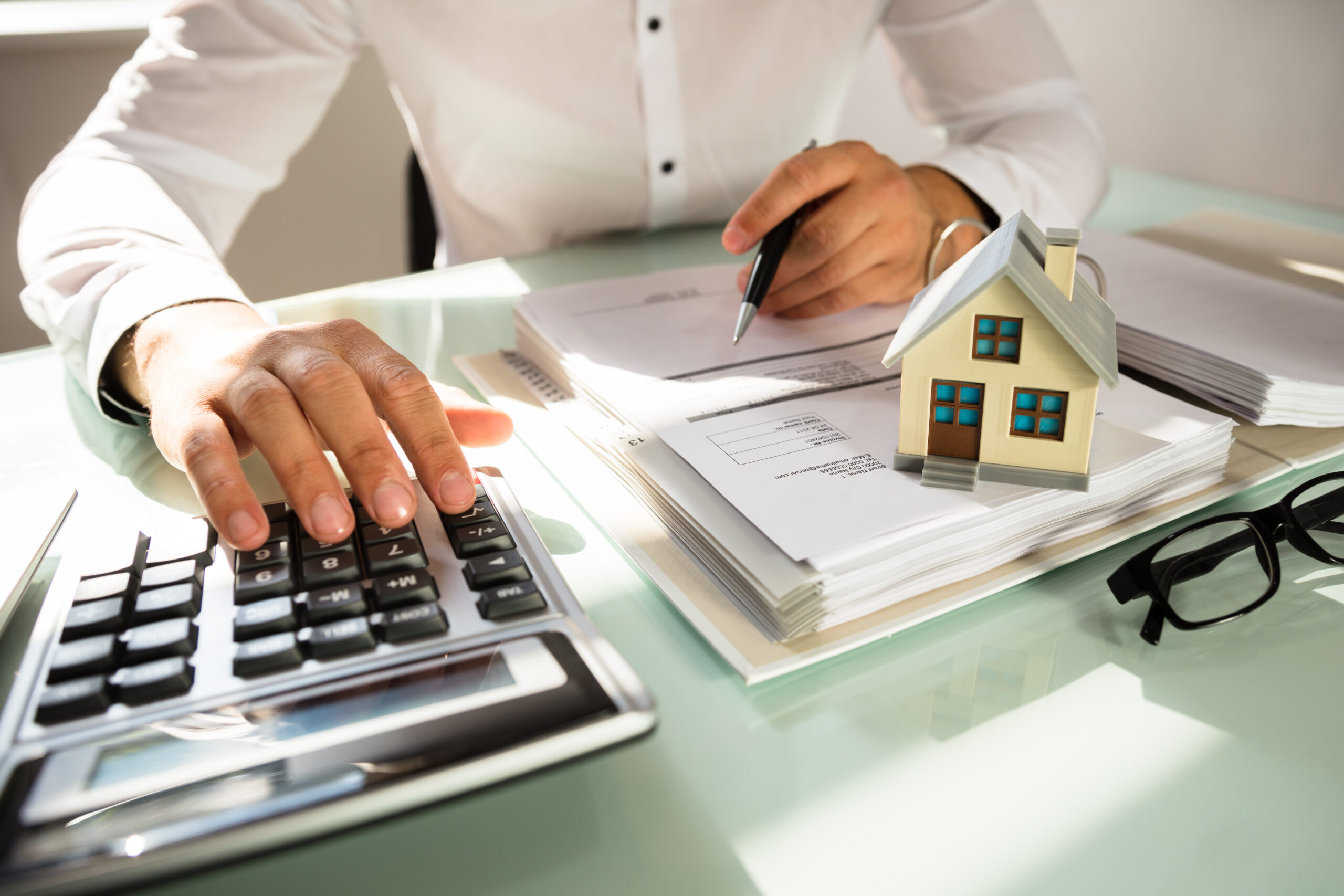 Businessman's,Hand,Calculating,Invoice,With,House,Model,In,Office